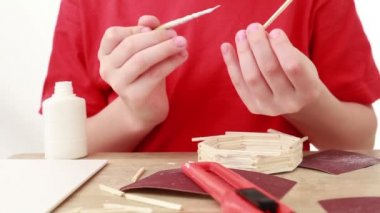 Boy apply glue on stick and attach it to wall of match house — Stock Video