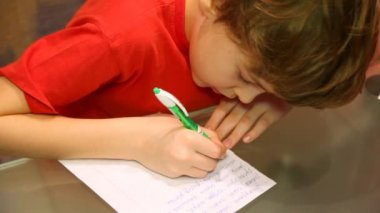 Top view of boy writes something. — Stock Video