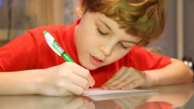 Boy writes something very attentively — Stock Video