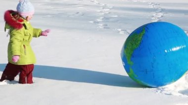 Girl push inflated ball, she fell down and sphere roll by snow further — Wideo stockowe