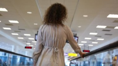 Woman moving on speedwalk and looks around at airport — Stock Video