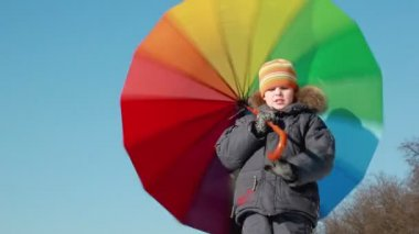 Boy stand and hold umbrella, he spins it by hook handle — Stock Video