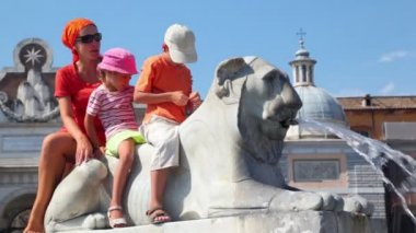 Mother and her kids sit on statue of lion near Flaminio obelisk — Stock Video