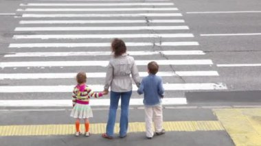 Mother and children, stand and wait to cross road at pedestrian crossing — Stock Video