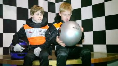 Boys sit in uniform for go-cart racing and wait the beginning of races — Stock Video