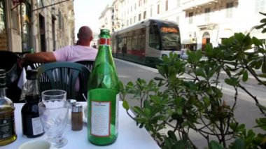 Tram arrives at the station and people come out of it, view from cafe table — Stock Video