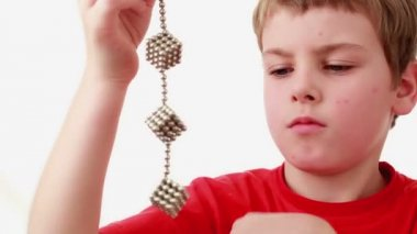 Boy hold chain compound of magnet spheres cubic structures — Stock Video