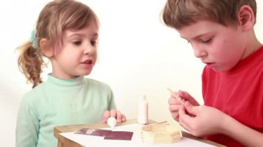 Girl tell something boy which apply glue on stick and attach to wall of match house — Stock Video