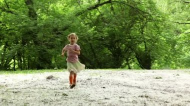 Girl runs closer across forest meadow all strewn fluff — Stock Video