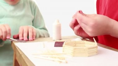 Two kids building match house, girl whet stick and boy glue — Stock Video