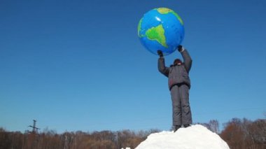 Boy stand on snow pile and hold inflated ball over head, then he throws it — Vídeo de stock