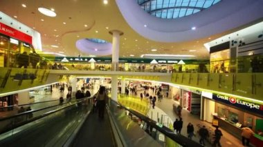 La gente se muda a las escaleras mecánicas en nuevas compras y entretenimiento centro troyka — Vídeo de Stock