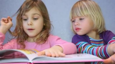 Two little girls read a picture-book — Stock Video