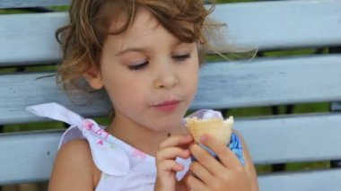 Little girl eat ice cream and sit on bench at park — Stock Video