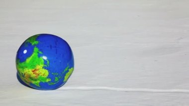 Inflated ball with earth texture roll by snow — Стоковое видео