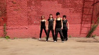 Dance team of four girls start dance synchronously, then fall down — Stock Video