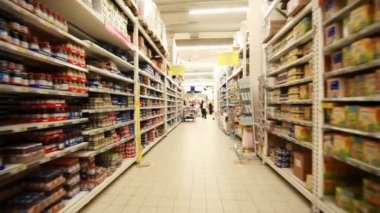 Stands with food in hypermarket, shooting from fast moving between them camera — Stock video