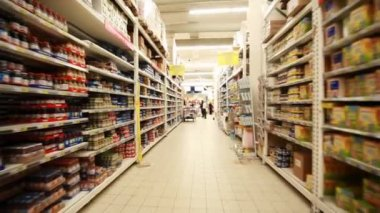 Stands with food in hypermarket, shooting from fast moving between them camera — Vídeo Stock