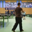 Children go round tables for table tennis in gym  — Stock Video