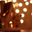 Toy house-candlestick stand at background of light spots — Stock Video
