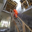 Workers carry huge plate by stairs to second storey — Stock Video