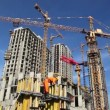 Builder works at against background of the construction site high-rise buildings — Stock Video