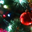 Stock Video: Glass toy ball reflects light rays on Christmas tree among of blinking garlands