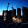 Stock Video: Night shift at construction site in foreground of dormitory arecityscape
