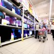 Family walk near showcase with many tv sets in hypermarket Auchan — Vídeo de stock #29829193