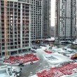 Stock Video: Workers and building materials at construction site in foreground of dormitory arecityscape