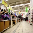 Few people walk among shelves with goods in hypermarket Auchan — Видео