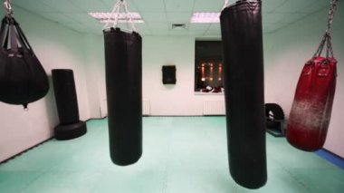 Four different size punching bag hang in boxing training room — Vídeo de stock