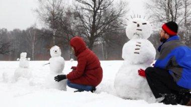 Mãe e pai com filha fazem três boneco de neve — Vídeo Stock