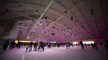 People skate on ice rink with colored illumination — Stock Video