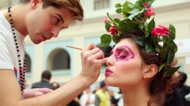 Man do makeup for model with flowers and leaves hair adornment at XVII International Festival World of Beauty 2010 — Stock Video
