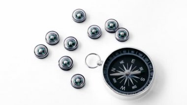 Nine small black plastic compasses and one big isolated — Stock Video
