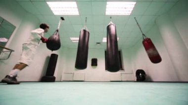 Man in gloves jumps and punches on light punching bag, then lot of hard at boxing gym — Stock Video