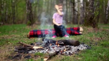 Little girl watch at bonfire burn, boy come and sit near — Stock Video