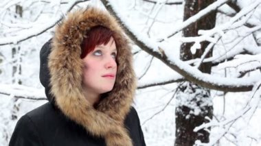Girl in fur hood looks at falling snow — Stock Video