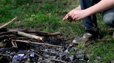 Little boy kindles bonfire with match, only legs are visible — Stock Video