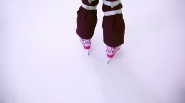 Little girl skates on ice rink, only legs are visible — Stock Video