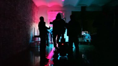 Operator with videocamera and film crew in almost dark room prepare scenery — Stock Video