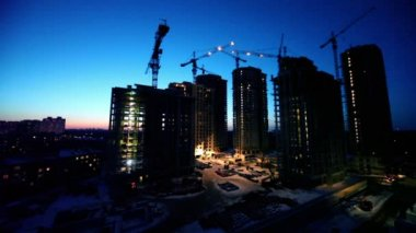 Night shift at construction site in foreground of dormitory area cityscape — Stock Video
