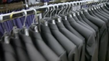 View of some identical jackets on hangers in shop — Stock Video