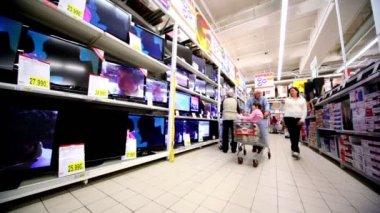 Rodina chodí poblíž vitrína s mnoha televizory v hypermarketu auchan — Stock video