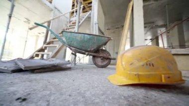 Helmet lies on floor in front of wheelbarrow — Stock Video