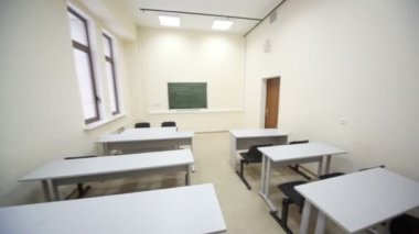 Empty classroom with wooden school desks and simple black chairs — Stock Video