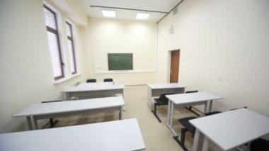 Пустой класс с Деревянные парты и простые черные стулья — Стоковое видео