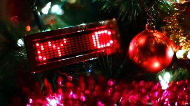 Toy ball and behind him LED display with running line MERRY CHRISTMAS on New Year tree — Stock Video