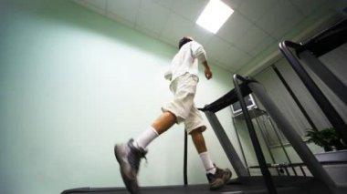 Man runs on treadmill near wall in gym — Stock Video